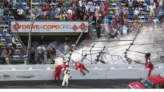 Rescue workers rush to the scene after Kyle Larson's car disinigrated into the catch fench at the finish line