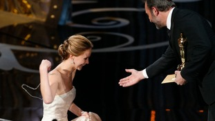 Jennifer Lawrence is helped by presenter French actor Jean Dujardin after she tripped