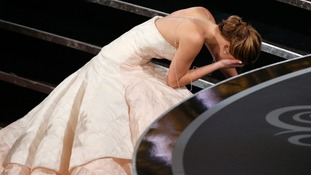 Jennifer Lawrence takes a tumble on stage as she goes to collect her award