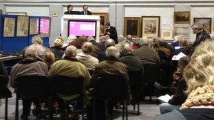 The auctioneers where the painting is waiting to go under the hammer