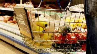 File photo of a shopper holding a shopping basket in a supermarket.