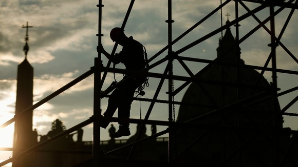 A worker sets up a structure for TV media in front of St Peter's Square in Rome