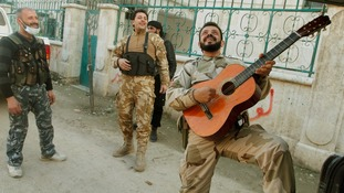 A member of the Free Syrian Army plays a guitar during a break in fighting.