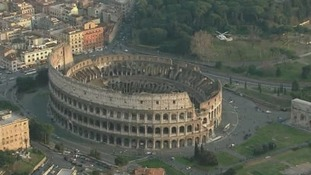 The Pope's helicopter pictured flying over Rome's Colosseum.
