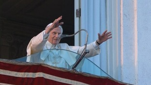 Pope Benedict XVI waves to the cheering crowds.