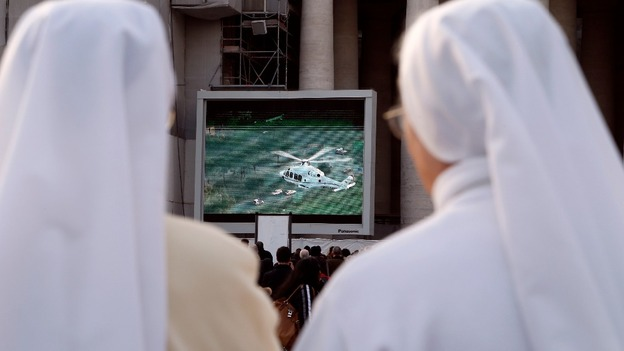 Nuns in Saint Peter's Square in Vatican City watch a giant screen of the helicopter carrying Pope Benedict XVI.