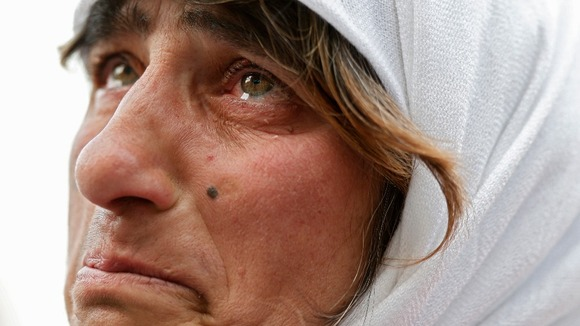 A woman cries as she watches the departure of Pope Benedict XVI on the giant screen.