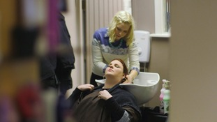 Lady washes hair of customer in hair salon