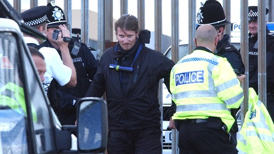 Undercover officer Mark Kenny is led away by police after being cut from the fence surrounding Hartlepool Nuclear Power Station