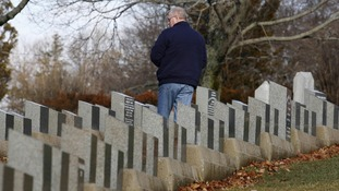 A visitor stands amid the gravestone of Titanic victims in Fairview Lawn Cemetery in Halifax