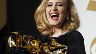 Singer Adele holds her six Grammy Awards at the 54th annual Grammy Awards in Los Angeles