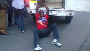 Photograph shows the taxi driver  tied to a police van.