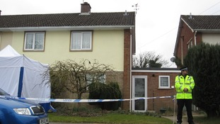 A police officer stands guard outside the property where the two bodies were discovered