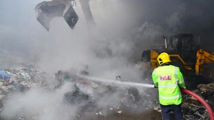 A firefighter douses burning rubbish at the site in Bickershaw