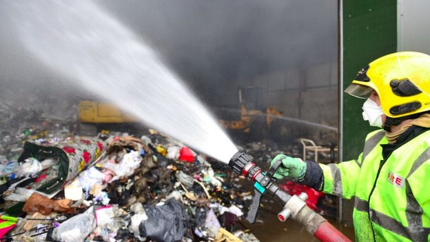 A firefighter douses the 76 tonnes of waste