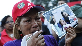 A supporter holds a picture of Chavez with his daughters, outside the military hospital where he died yesterday.