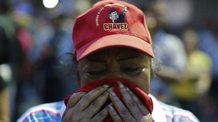 A woman reacts to the news of the death of Hugo Chavez