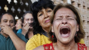Supporters of Hugo Chavez react to the annoucement of his death outside his hospital in Caracas.