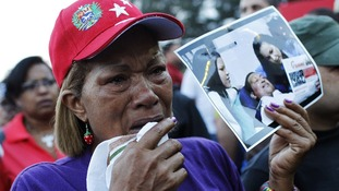 A supporter holds a picture of Chavez with his daughters, outside the military hospital where he died yesterday