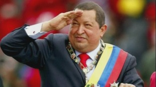Hugo Chavez salutes during a military parade