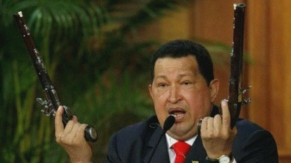 Hugo Chavez wields two guns which used to be owned by Simon Bolivar