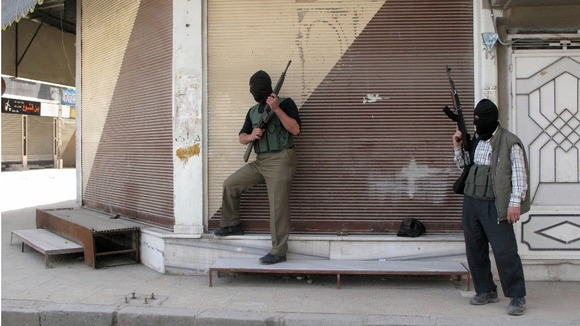 Free Syrian Army fighters stand guard during fighting with Syrian troops in a suburb of Damascus
