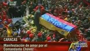Hugo Chavez's casket is loaded onto the hearse before being driven through the streets of Caracas