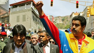 Venezuela's Vice President Nicolas Maduro (R) and Bolivia's President Evo Morales join the mourners in the streets of Caracas