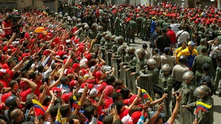 Venezuelan riot police hold back mourners hoping to ctach a glimpse of Hugo Chavez's coffin travelling through the streets of Caracas