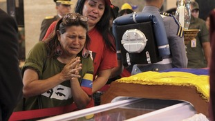 Mourners cry as they pay their respects as the body of Hugo Chavez lies in state