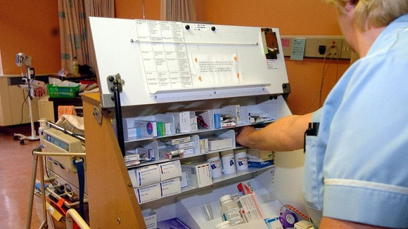 A member of the nursing staff dispensing drugs from a trolley on a ward