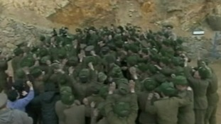 Kim Jong-un can barely be seen amongst the cheering crowd of soldiers