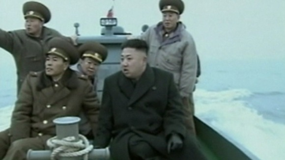Kim Jong-un arriving on the island to be greeted by soldiers