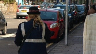 female traffic warden and parked cars
