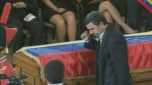 Iran's President Mahmoud Ahmadinejad gestures to the other guests at the funeral