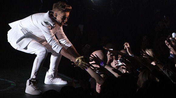 Justin Bieber greets fans on stage at the O2 Arena in London after appearing up to two hours late