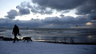 A man walks his dog in Tynemouth after more overnight snow