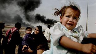 A little girl is held as families flee Basra