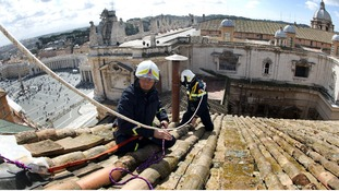 Under sunny skies fire-fighters set up the chimney on the roof of the Sistine chapel ahead of the cardinals conclave