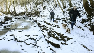 Dog walkers at the Bow Lee Beck waterfall at Gibson's Cave in Teesdale which has frozen