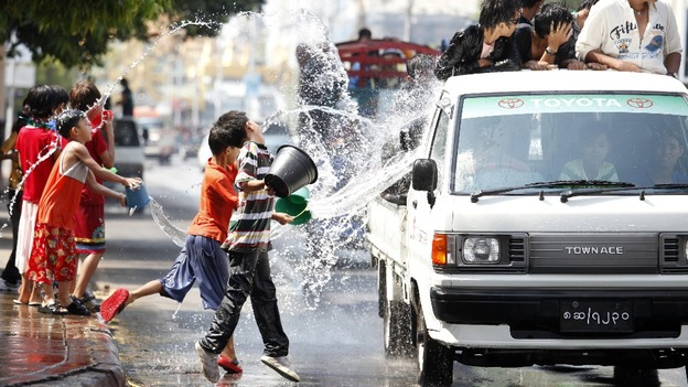 Children throw water at passing traffic in central Yangon
