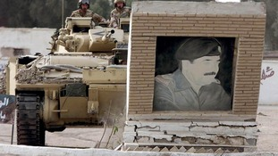 A British Warrior armoured combat vehicle drives into a picture of Saddam Hussein in the city of Basra.