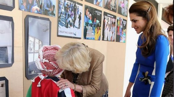 Duchess of Cornwall talks to a pupil at the Mahis Secondary School as Jordan&#x27;s Queen Rania looks on