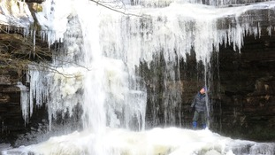 A man looks at the icicles formed on the Bow Lee Beck waterfall at Gibson's Cave in Teesdale.