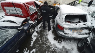 A police officer stands among the wrecked vehicles.