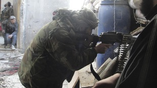 A Free Syrian Army fighter aims his weapon in the Al-Khalidiya neighbourhood of Homs