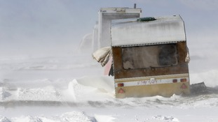 An abandoned caravan is buffeted by winds and drifting snow on the South Downs near Brighton