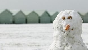 A snowman surveys the wintry vista on Brighton beach