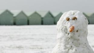 A snowman surveys the wintry vista on Brighton beach