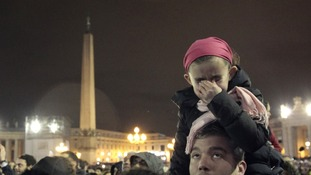 A girl cries as she waits with thousands to greet the new pope.